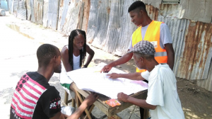 Mapping and verification assistant Akeem, who was promoted to Junior Land Surveying Technician, sharing his map with community members for their feedback and corrections.